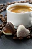 Espresso, coffee beans and chocolate candies in a heart shape — Stockfoto