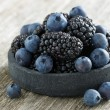 Bowl of fresh blackberries and blueberries on wooden background — Stock Photo #64031497
