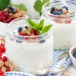 Yogurt with fresh berries and breakfast foods on table, close-up — Stock Photo #64196673