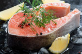 Raw salmon steak with dill and lemon on ice, close-up — Fotografia Stock