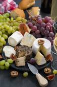 Soft delicacy cheeses and snacks for wine on a dark background — Stock Photo