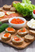 Appetizers - toast with salted salmon and red caviar — Stock Photo