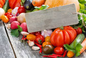 Assorted fresh seasonal vegetables and a wooden nameplate for te — Stock Photo