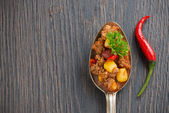 Mexican dish chili con carne in a spoon on a wooden background, — Stock Photo