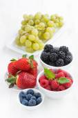 Fresh garden berries and grapes on a white wooden table, vertica — Stock Photo