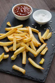 Fried French fries, tomato sauce and salt on a blackboard, top v — Stock Photo
