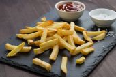 Fried French fries, tomato sauce and salt on a blackboard — Stock Photo