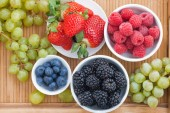 Fresh berries in a bowl and green grapes on wooden tray, top vie — Stock Photo