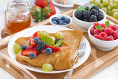 Delicious breakfast - crepes with fresh berries and honey on woo — Stock Photo