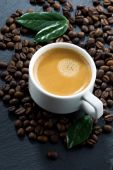 Cup of espresso on coffee beans background, top view — Stock Photo