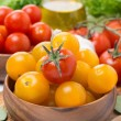 Yellow and red cherry tomatoes in wooden bowls, close-up — Stock Photo #72170061