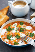 Fried quail eggs in tomato sauce in a frying pan for breakfast — Stock Photo