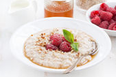 Plate of oatmeal with fresh raspberries and honey, close-up — ストック写真