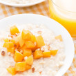 Постер, плакат: Oatmeal with fresh apricots and nuts orange juice top view