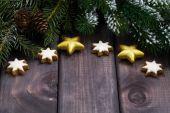 Tmavé dřevěné pozadí s větvemi jedlí, cookies a dekorace — Stock fotografie