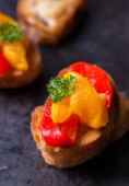 Bruschetta with grilled bell pepper over old dark tray — Stock Photo