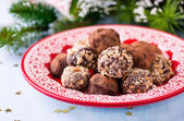 Assorted dark chocolate truffles on red plate — Stock Photo