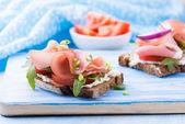 Open sandwiches with ham, tomato and arugula — Stock Photo