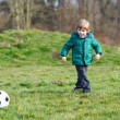 Little boy playing football or soccer on cold day — Stock Photo #52043337