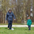 Young father with his little son playing football on playground. — Stock Photo #52043513