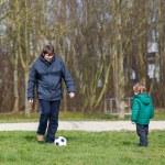 młody ojciec z synem trochę gry w piłkę nożną na boisku — Zdjęcie stockowe #52043513