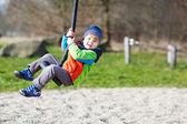 Sonriente niña de dos años divirtiendo en swing en frío da — Foto de Stock