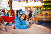 Adorable little child on a carousel at Christmas funfair or mark — Stock Photo