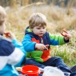 Two little sibling boys having picnic near forest lake, nature — Stock Photo #52858593