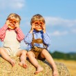 Two little sibling boys and friends sitting on hay stack  and ea — Stock Photo #52859441