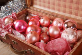 Ancient pink Christmas tree toys in antique suitcase — Stock Photo