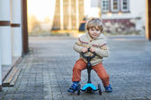 Little toddler boy riding and his scooter bicycle in summer  — Stock Photo