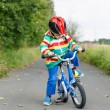 Adorable kid boy in red helmet and colorful raincoat riding his — Stock Photo #52860343