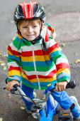 Adorable kid boy in red helmet and colorful raincoat riding his  — Stock Photo