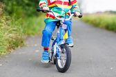 彼の最初の自転車に乗ってカラフルなレインコートの子供 — ストック写真