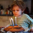 Adorable four year old boy celebrating his birthday and blowing — Stock Photo #53753709