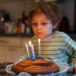Adorable four year old boy celebrating his birthday and blowing — Stock Photo #53753741