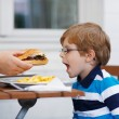 Little boy eating fast food: french fries and hamburger — Stock Photo #53754251