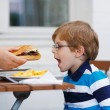 Little boy eating fast food: french fries and hamburger — Stock Photo #53754295