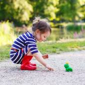 Beautiful little girl in red rain boots playing with rubber frog — Stock Photo