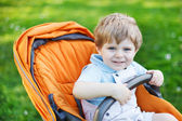 One lovely caucasian toddler boy of two years sitting in pram on — Stock Photo