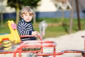 Little toddler boy having fun on old carousel on outdoor playgro — Stock Photo