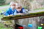 Two little brothers playing with paper boats by a river — Stock Photo