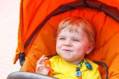 Funny toddler boy smiling outdoor in orange stroller  — Stock Photo