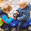 Two little sibling children playing with toy car on autumn day. — Stock Photo #53760625