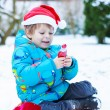 Happy little toddler boy waiting for Christmas santa hat — Stock Photo #55577749