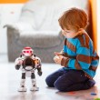 Little blond boy playing with robot toy at home, indoor. — Stock Photo #55581071