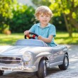 Little boy driving big toy old car, outdoors — Stock Photo #55581189