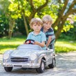 Two happy children playing with toy car — Stock Photo #55581195