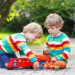 Two siblings, kid boys playing with red school bus — Stock Photo #55583515