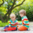 Two little children playing with red school bus — Stock Photo #55583877